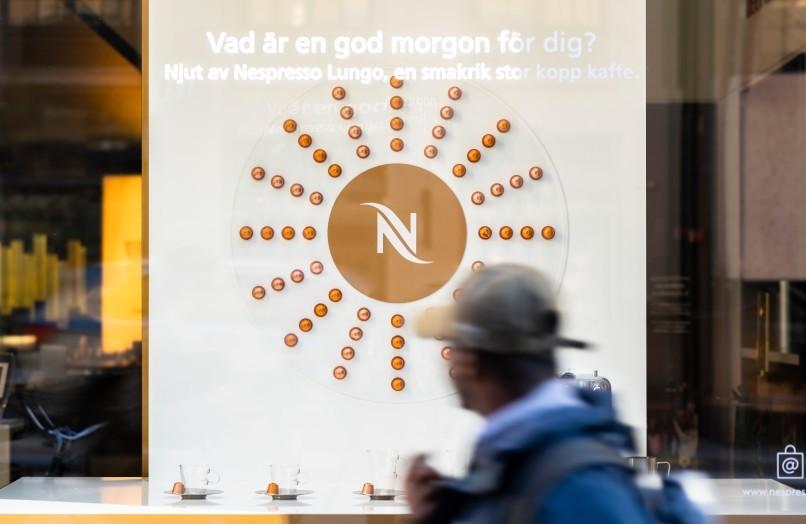 Förbpaserande tittar på skyltfönsterdesignen av WorkShop i Nespresso Store på Kungsgatan.
